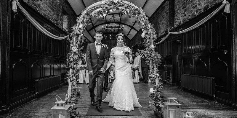 bride and groom under flower arch