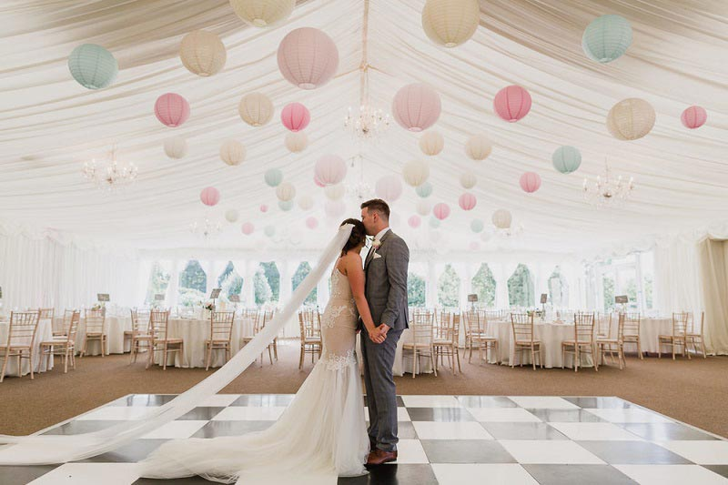 wedding couple in marquee decorated with lanterns