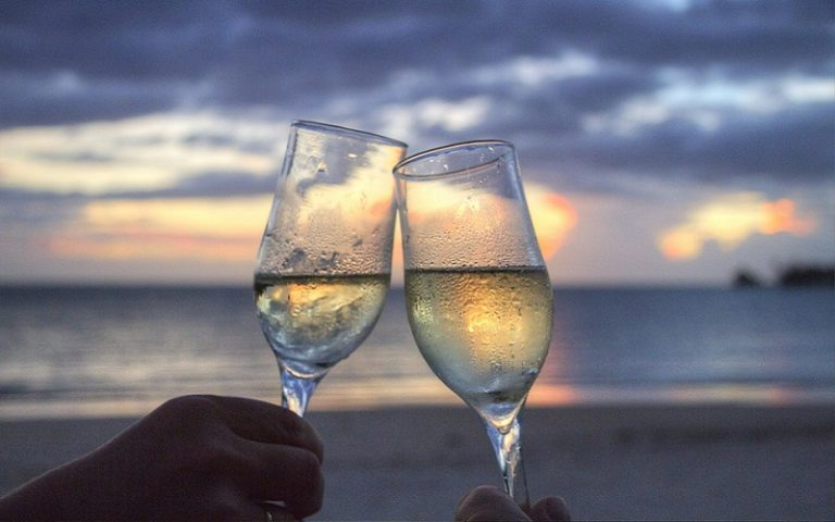 wine glasses clinking on beach