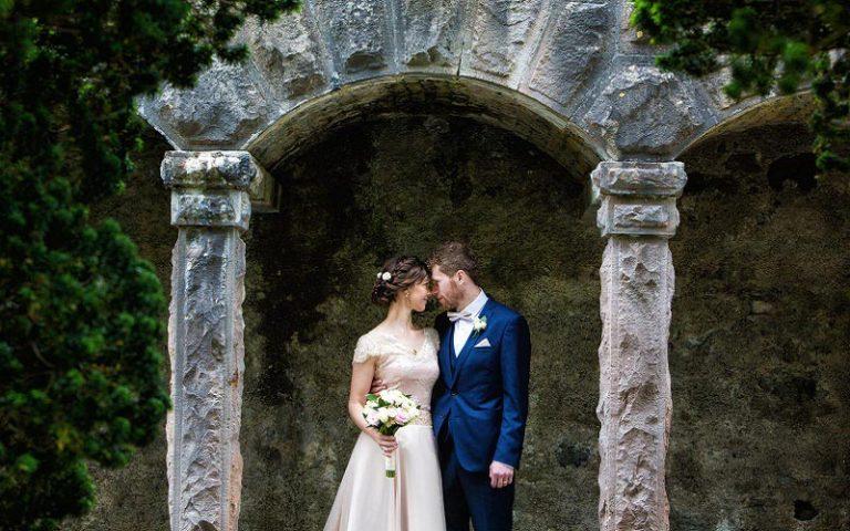 bride and groom under arcg